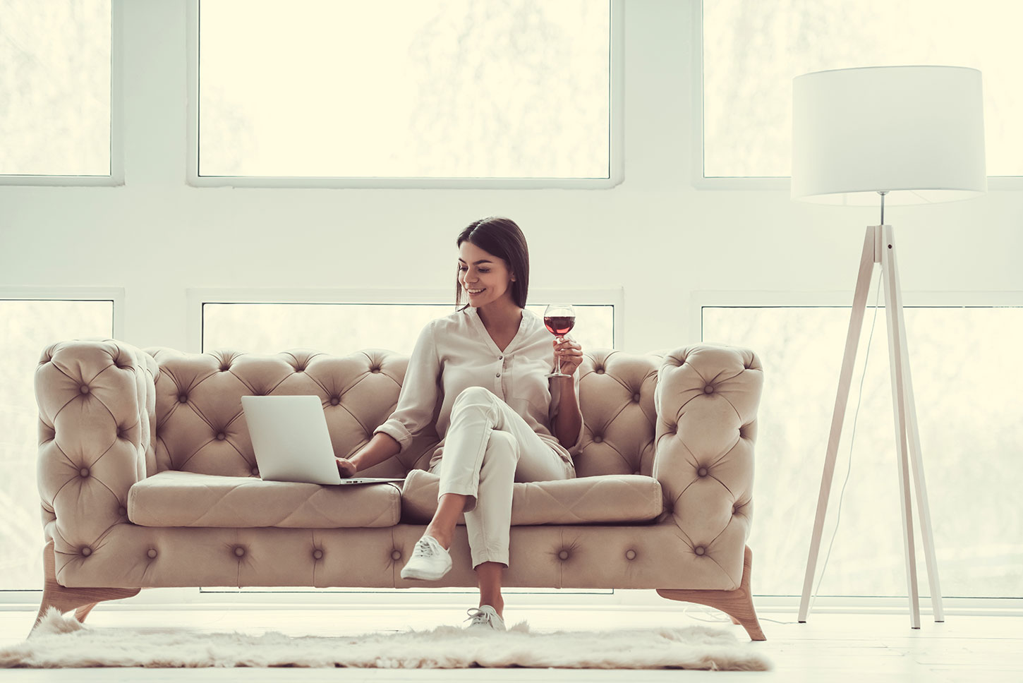 Woman drinking red wine on couch.